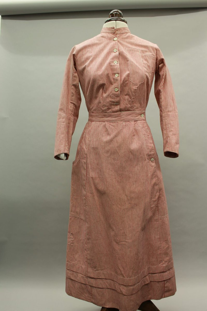 This dress is one of two domestic service dresses kept in the collection at Preston Park Museum and Grounds. It's a heavy garment made from red and white striped cotton twill, a robust material made to take lots of wear and tear. It has 6 pearl buttons down the front with a high neck fastening.   Image courtesy of Preston Park Museum and Grounds.