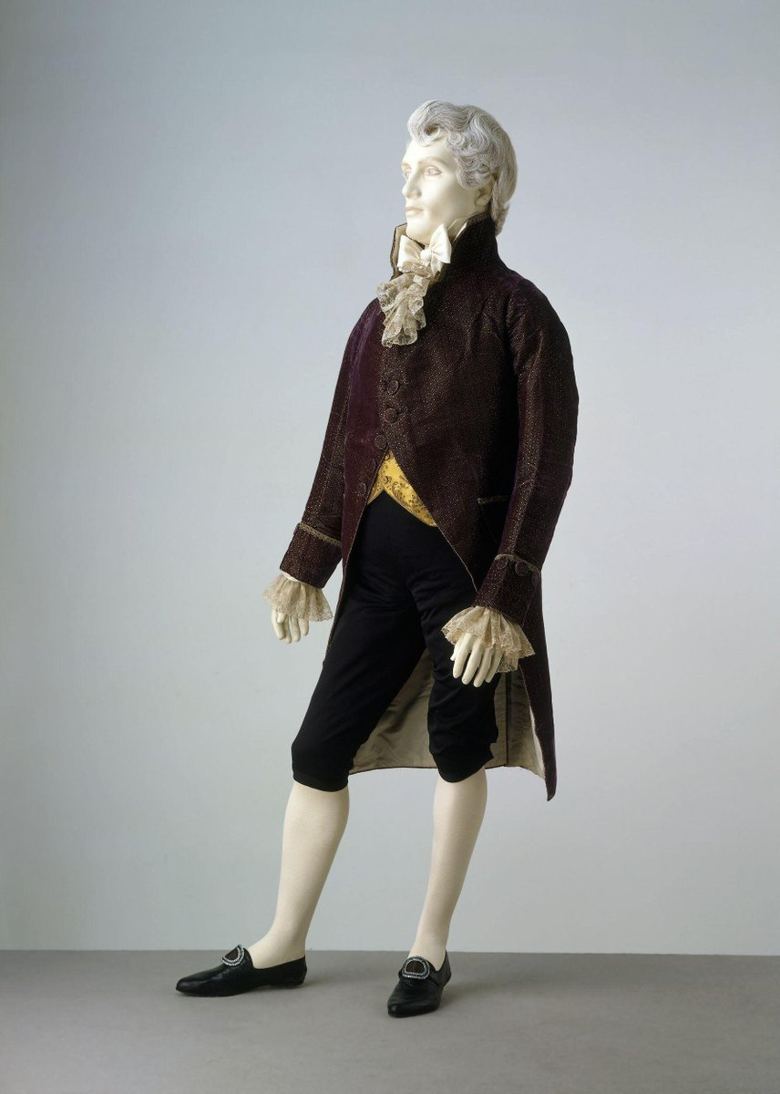 ©Victoria and Albert Museum, London - Man's coat of purple silk velvet with a triangular and chequered woven figured pattern. The top of the cuff and pockets and collar are covered with looped gilt braid. The coat is lined with silk quilted at chest and shoulders. The buttons are self covered and only the two on the apex of the very convex chest can be fastened. Hand-sewn.