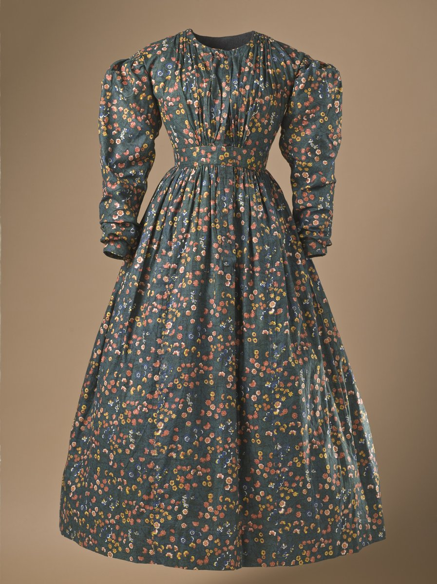 1836, cotton dress, plain weave printed calico. Background color, green: orange and yellow printed small flowers. Puffy sleeves, rushed bodice. Slightly more pronounced flair to the skirt.