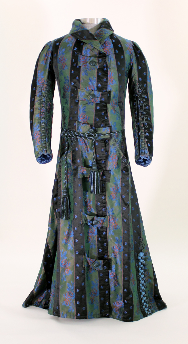 Man's full length, long sleeve dressing gown. Large folded-over lapels around neck and down front. Buttons across chest, rope belt at waist. Gown alternating stripes of silk fabric - black with small embroidered design and olive green with blue and pink embroidered floral pattern. - From the Lichfield Historical Society