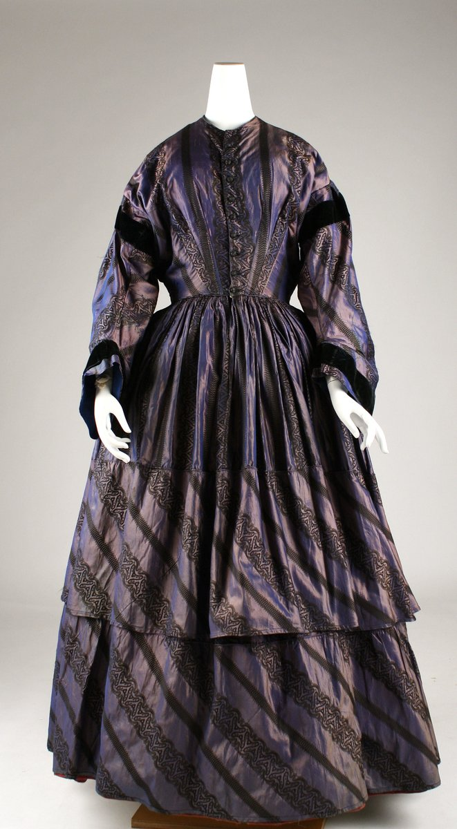 Afternoon dress in shot silk/changeable silk, with horizontal stripes. Narrow waist, long sleeves, loose. Loose tailoring.