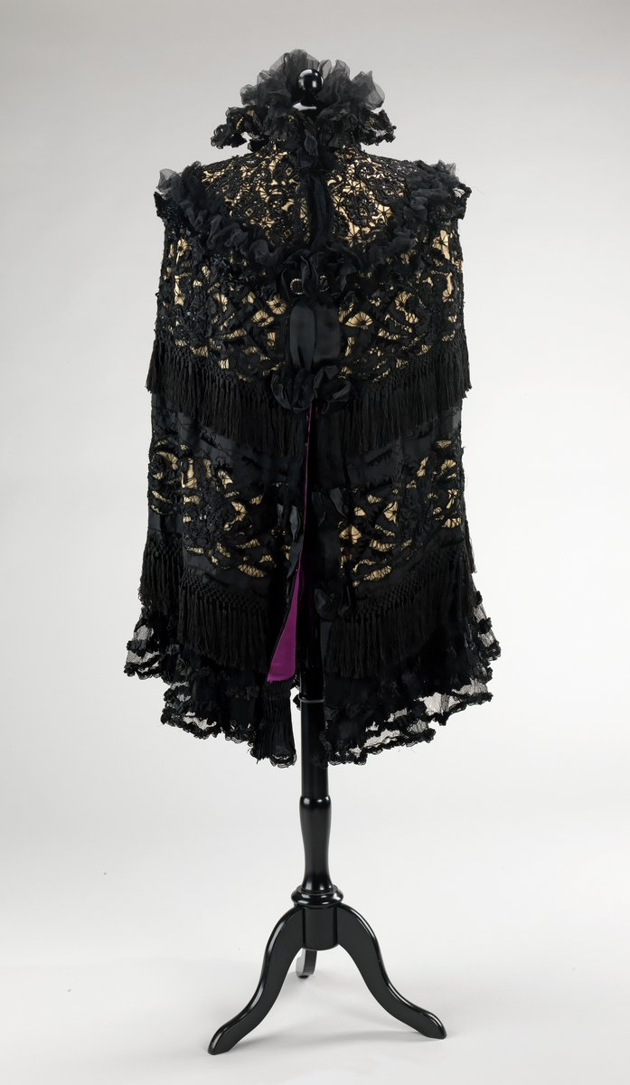 A crepe and lace cape with frills at the neck and shoulder, and then alternating lines of lace and crepe stripes. It is lined in purple silk. Via the Met.