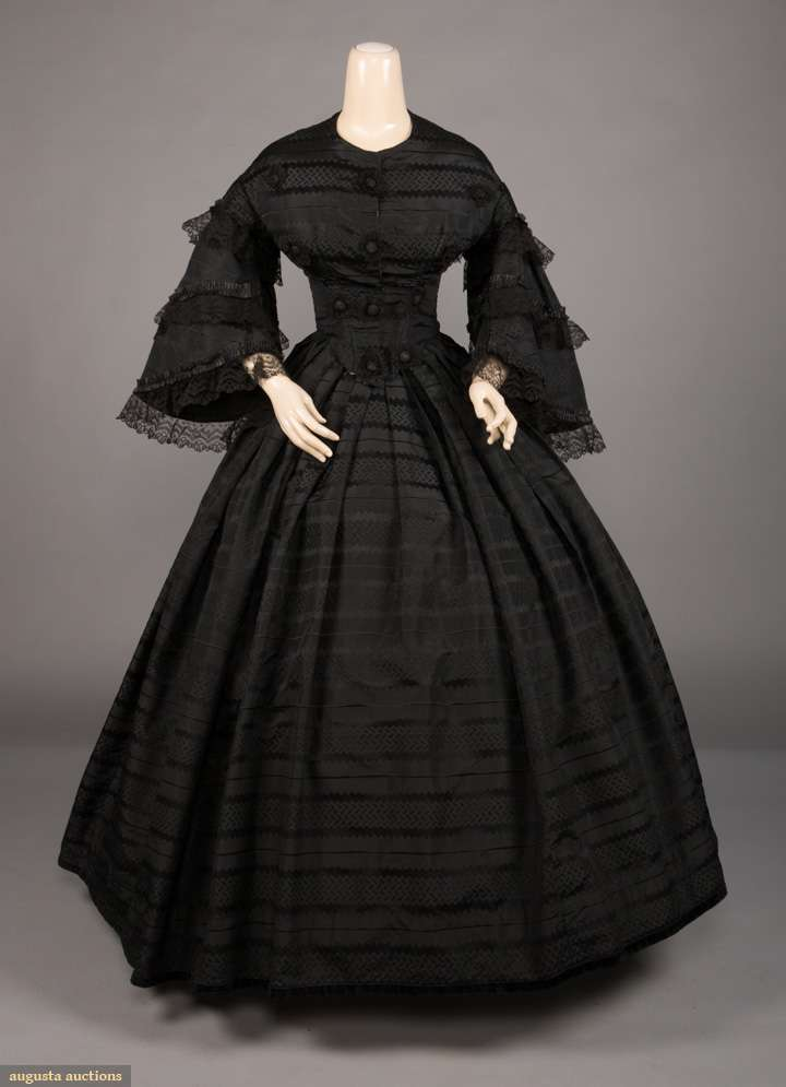 2-pc black silk 1860s evening gown w/ black geometric stripes & Chantilly lace trim to pagoda sleeves, bodice accented w/ lace rosettes on self-fabric decorative button at CF, (side seams taken in, missing hooks, holes in lace on sleeves, light white stain in CB hem) very good. Augusta Auctions.