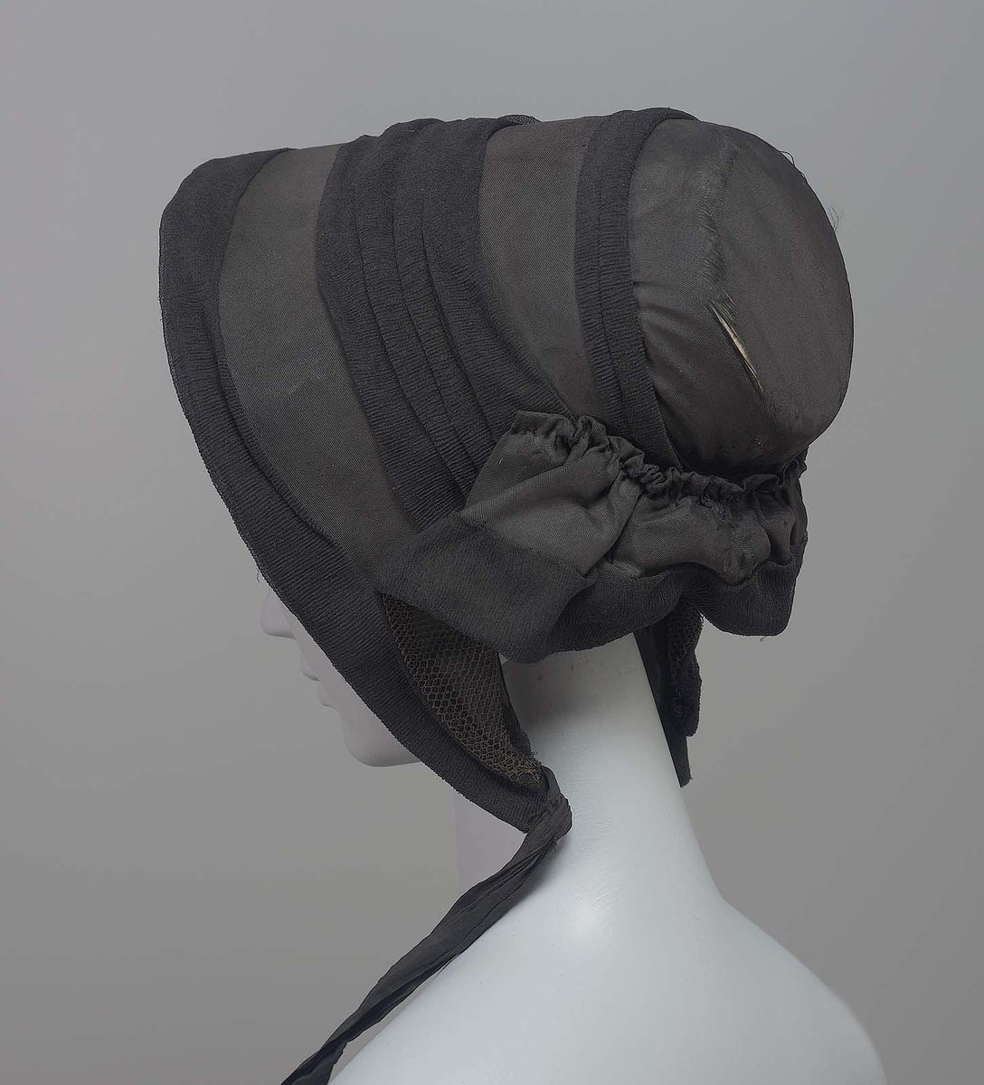 Mourning bonnet, black slightly ribbed silk trimmed with folds of black crèpe, one black ribbon tie, (other tie missing).