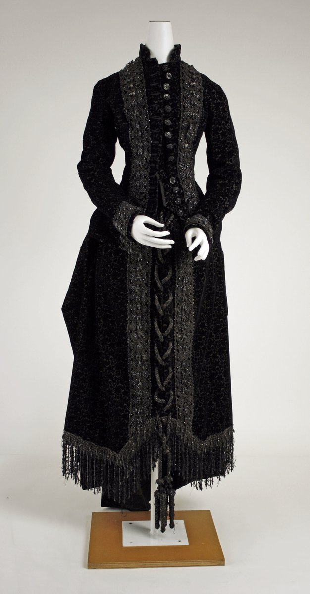 A classic high-collared 1880s silhouette gown, but with tons of beading, and beaded fringe. Big buttons down the center, a braided-like center as well. From the Met.