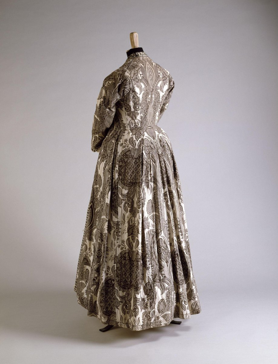 © Victoria & Albert Museum - Gown (wentke) of painted and dyed cotton chintz. With a pattern of large palmette flanked by foliate scrolls. Flowers fill the intervening spaces. Both flowers and leaves are patterned with floral meanders and zig zag motives. Hindelopen cut and the seams are accented by a line of backstitching in black floss silk. Lined with white linen. The neck, fronts and wrists are edged with black and white weft patterned tape.