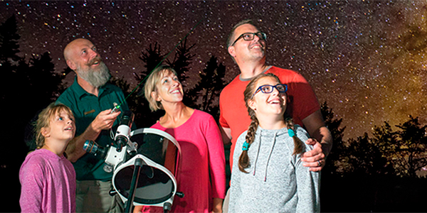 A family with a guide looking into the night sky, Kejimkujik National Park and National Historic Site.