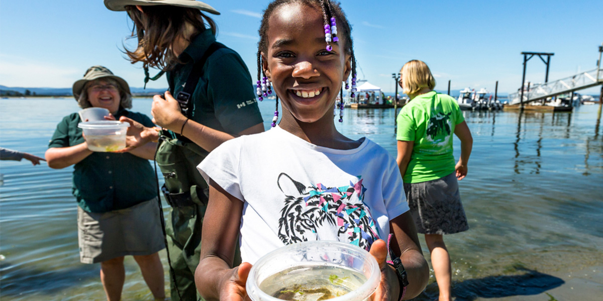 A young volunteer shows a fish caught during a species survey at the beach.