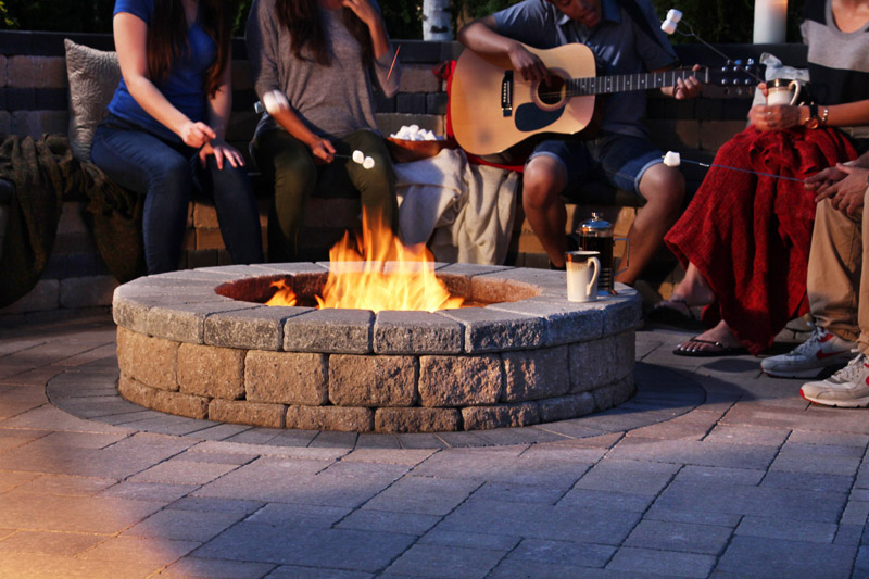 playing guitar around a firepit