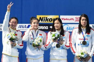 Team China celebrates its gold medal during the podium ceremony for the women's 4x100m medley relay swimming event at the 2015 FINA World Championships in Kazan on August 9, 2015. Shi Jinglin, Lu Ying, Fu YuanHui and Shen Duo competed in the event. AFP PHOTO / FRANCOIS XAVIER MARIT (Photo credit should read FRANCOIS XAVIER MARIT/AFP/Getty Images)