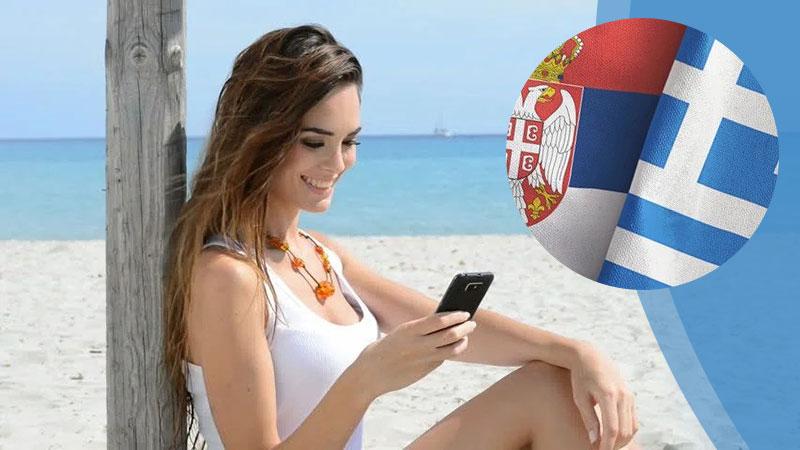 Devojka sa telefonom na plaži i zastave Grčke i Srbije