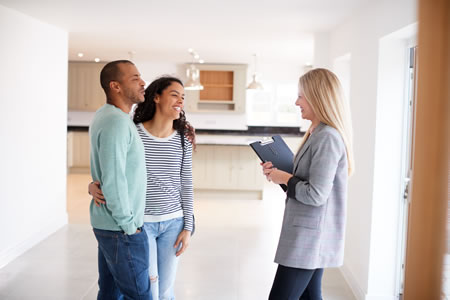 Woman realtor showing couple home