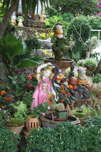 Garden with flowers and small statues of Buddhist and other religious figures