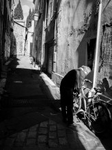 An elder gentleman parking and securing his bicycle in a small sidestreet in the center of Arles
