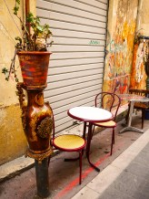 Unique flower pot and a couple of tables outside a tiny caffe