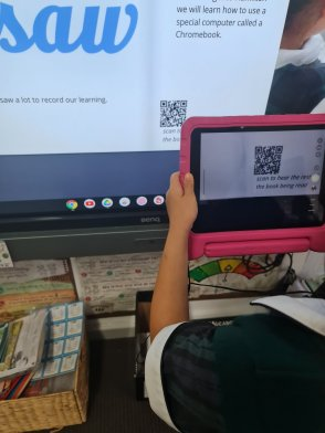 a person scanning a QR code on a projected screen from a tablet