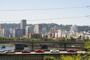 Cars in traffic with downtown Portland in the background.
