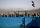 A young man jumps from a diving board into a swimming pool on a hill overlooking Kabul, on May 17, 2013. The swimming pool build by the Soviets more then 30 years ago has rarely been used caught instead in the middle of decades of war. (AP Photo/Anja Niedringhaus) #