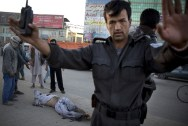 An Afghan policeman pushes people away after a bomb exploded under a car, leaving the driver dead, in the center of Kabul, on October 21, 2013. The Afghan Interior ministry confirmed that it was a magnetic bomb that destroyed the vehicle and killed the driver in the early morning rush hour. (AP Photo/Anja Niedringhaus) #