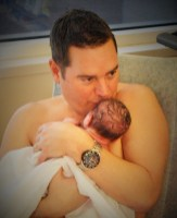 Father without shirt sitting with newborn on chest for skin to skin