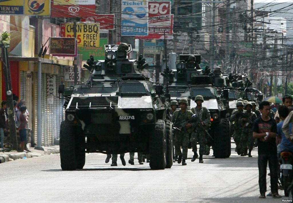 While civilians are fleeing for their lives, elements of the Armed Forces of the Philippines (AFP) engage Moro rebels in a Zamboanga City street, backed-up by light armor vehicles popularly known as Simba. 13 September 2013. CNA Photo.