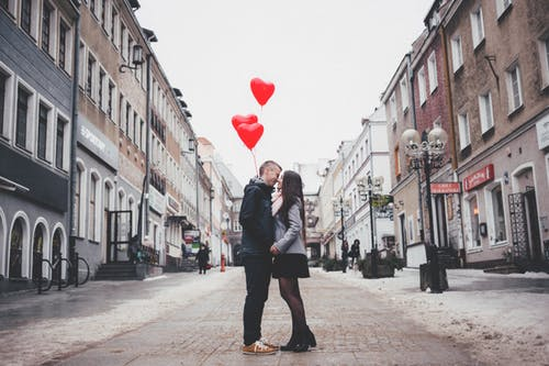 A happy couple kissing on a beautiful street signifying that teens should have domestic violence in mind