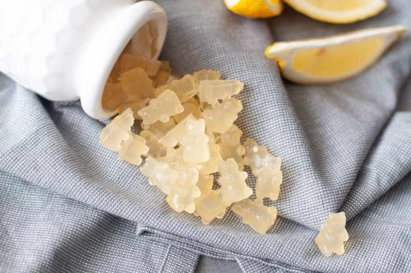 An overhead shot of a milky white bottle layering on its side, spilling out a bunch of freshly made Sour Lemon Gummy Snacks on a gray cloth napkin. The gummies are shaped as tiny bears, and garnished with a fresh cut lemon.