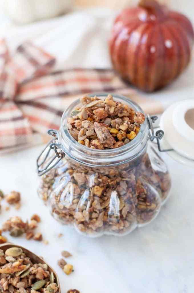 Gluten Free Pumpkin Spice granola in a decorative glass jar, shaped like a pumpikin