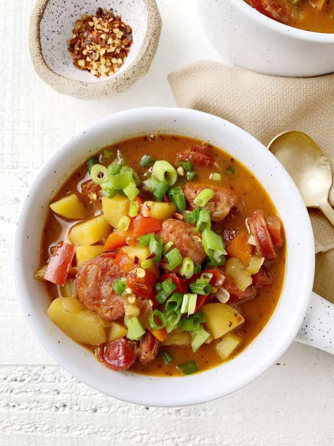 overhead shot of a really colorful bowl of whole30 cajun soup - peppers, celery, sausage, onions, potatoes