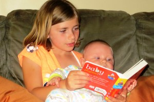 9-years old, reading to her baby brother.