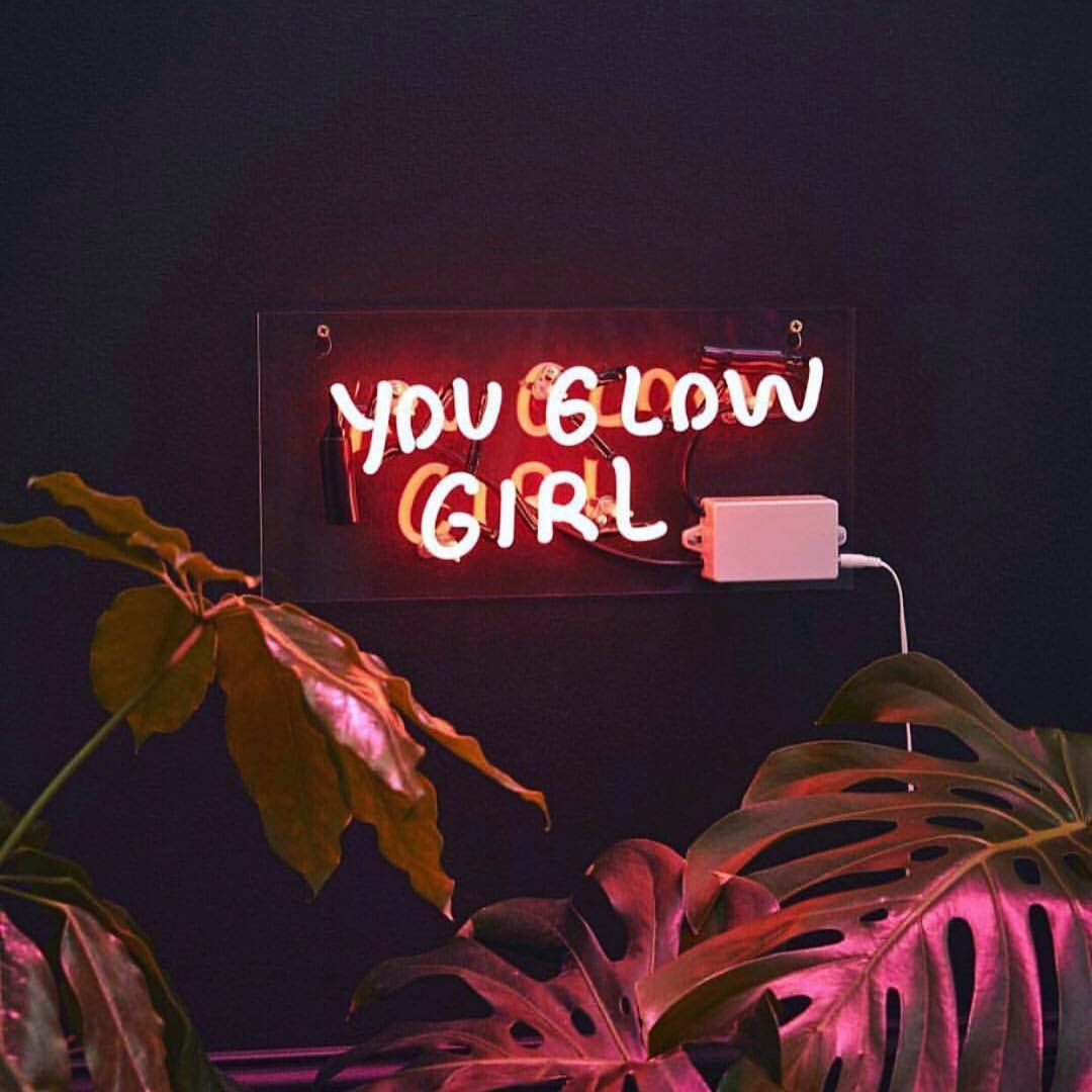 "a sign saying ""you glow girl"" in pink"