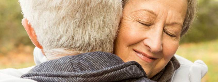 peace-mind-transitions-senior-moves-simple-life-packed-boxes-elderly-couple-hug
