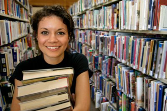 female holding a stack of books in the library