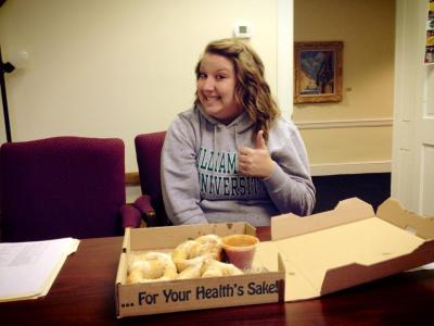 Transfer student smiling next to a box of doughnuts.