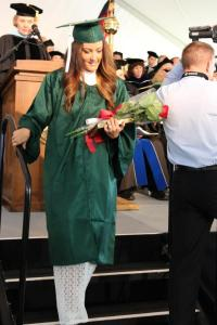 student walking down steps of graduation stage holding flowers