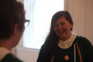 student in graduation gown looking away and laughing