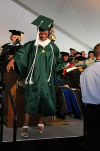 student laughing on graduation stage in gown