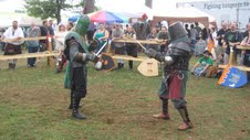 two soldiers dressed in full armor sword fighting
