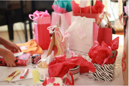 Multiple pink and red colored gift packages sit on a table with candy