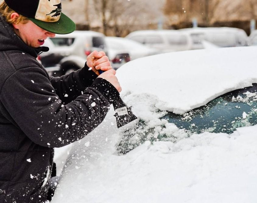 Christian Neal struggles to scrape ice and snow off of a vehicle