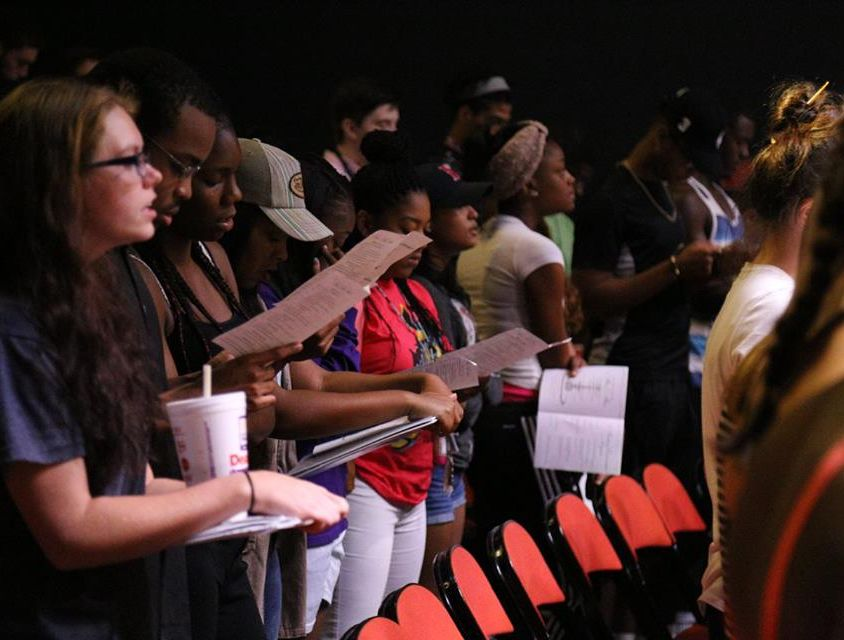 Group of freshmen students stand reading pamphlets at convocation