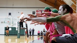 group of green and white painted students sit in the bleachers in the gymnasium cheering