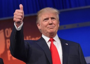 Donald Trump holds a thumbs against a blue background