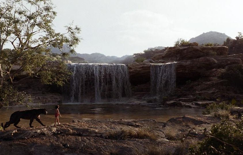 Small boy is followed by a black panther amidst scenic, waterfall landscape