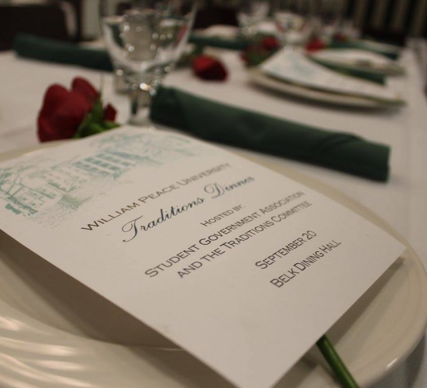 Small card of text laid ontop of a plate with a table set with red roses, white tablecloths, and green linens.