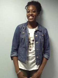 female student Rebecca Tshibambi stands smiling in a denim jacket against a white background
