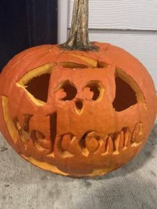 pumpkin carved with an owl with the text 'Welcome'