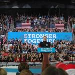Musician Lady Gaga stands behind a poduim in a crowded room with a banner reading ;'Stronger Together' behind her.