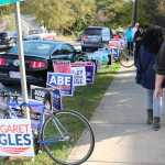 Groupf of students walk on a sidewalk past a row of political signage on the street