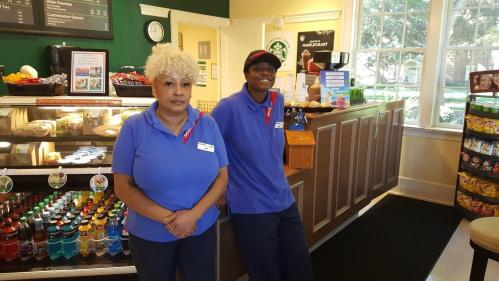 Eugeina Collins stands to the left of Tameka Talley, both dressed in blue Sodexo uniforms with Peace Perk in the background